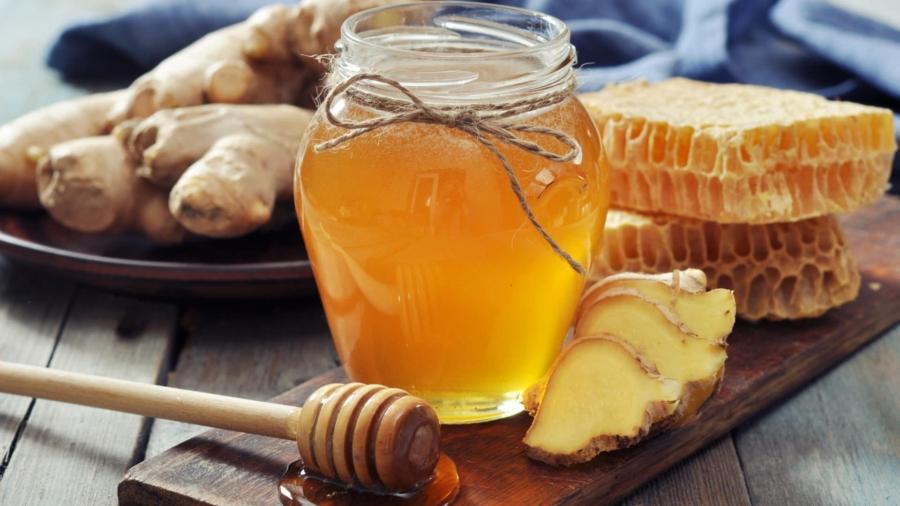 Honey in jar with fresh ginger on vintage wooden background